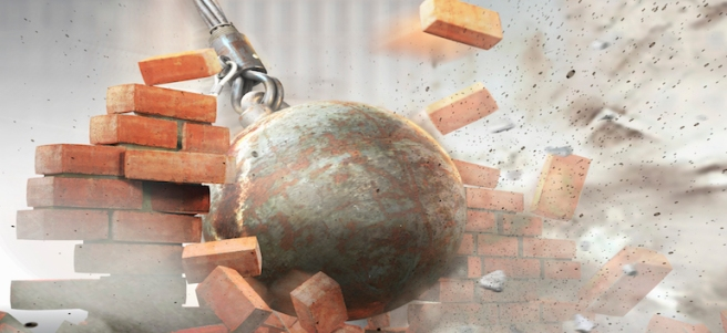 Wrecking ball hitting an demolishing brick wall